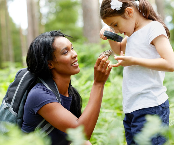Woman and Child Looking at Pine Cone