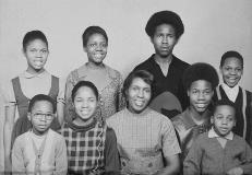Davis, wearing glasses in the bottom left hand corner of this undated family photo, grew up in the Hough neighborhood and was exposed to violence at a young age.
