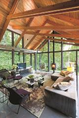 The Farrells achieved a modern-day tree house vibe with a high-arched, wooden beam ceiling and walls of windows all around.